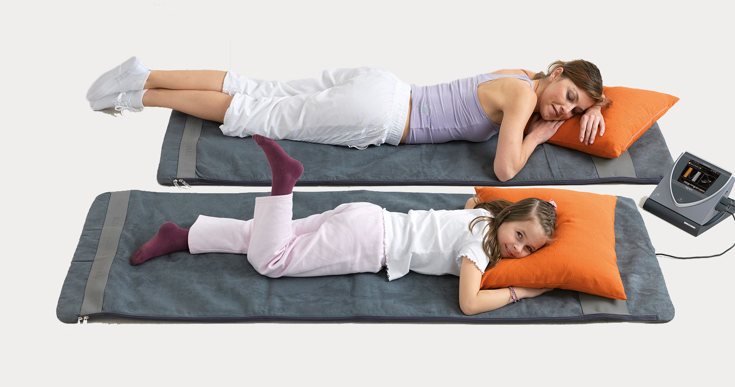Two people lay on BEMER mats