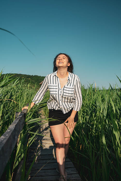 Woman happily walking through sunny field