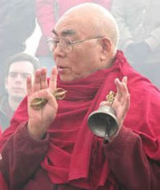 Lama Lodu Rinpoche in red robes, giving blessing