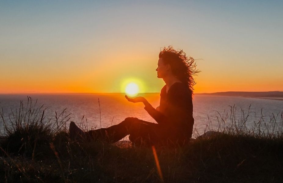 Woman holding sunset over ocean