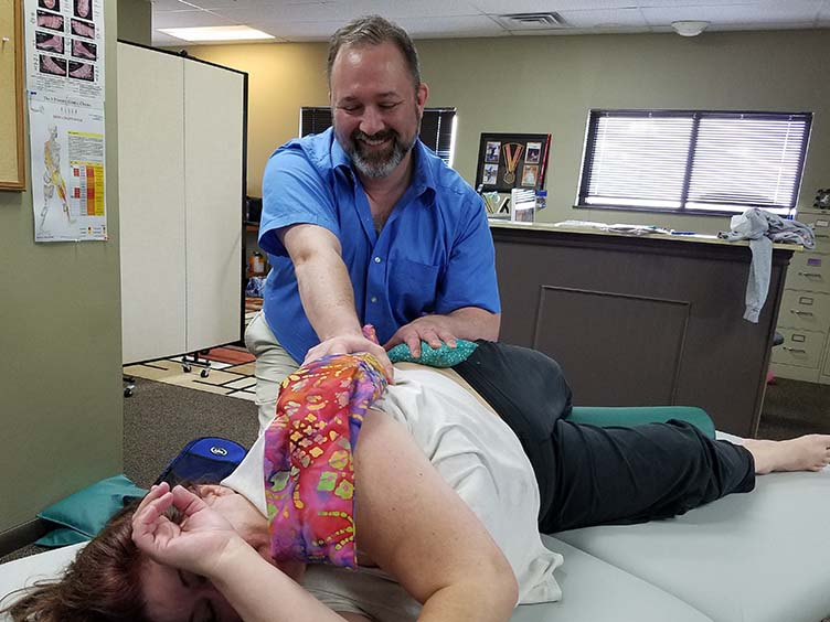 Jason Erickson demonstrates using hot flax pillow with massage to ease client's pain
