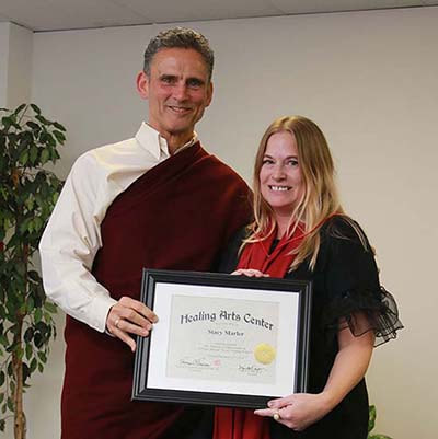 Stacy Marler receives her certificate of completion from Headmaster, Tom Tessereau, from the Massage Program at the Healing Arts Center